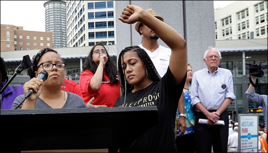 Marissa Johnson, left, speaks as Mara Jacqueline Willaford holds her fist overhead and Democratic presidential candidate Sen. Bernie Sanders, I-Vt., stands nearby as the two women take over the microphone at a rally Saturday, Aug. 8, 2015, in downtown Seattle. The women, co-founders of the Seattle chapter of Black Lives Matter, took over the microphone and refused to relinquish it. Sanders eventually left the stage without speaking and instead waded into the crowd to greet supporters. (AP Photo/Elaine Thompson): https://jamieutt.files.wordpress.com/2015/08/dem2016sanders_cata.jpg?w=682